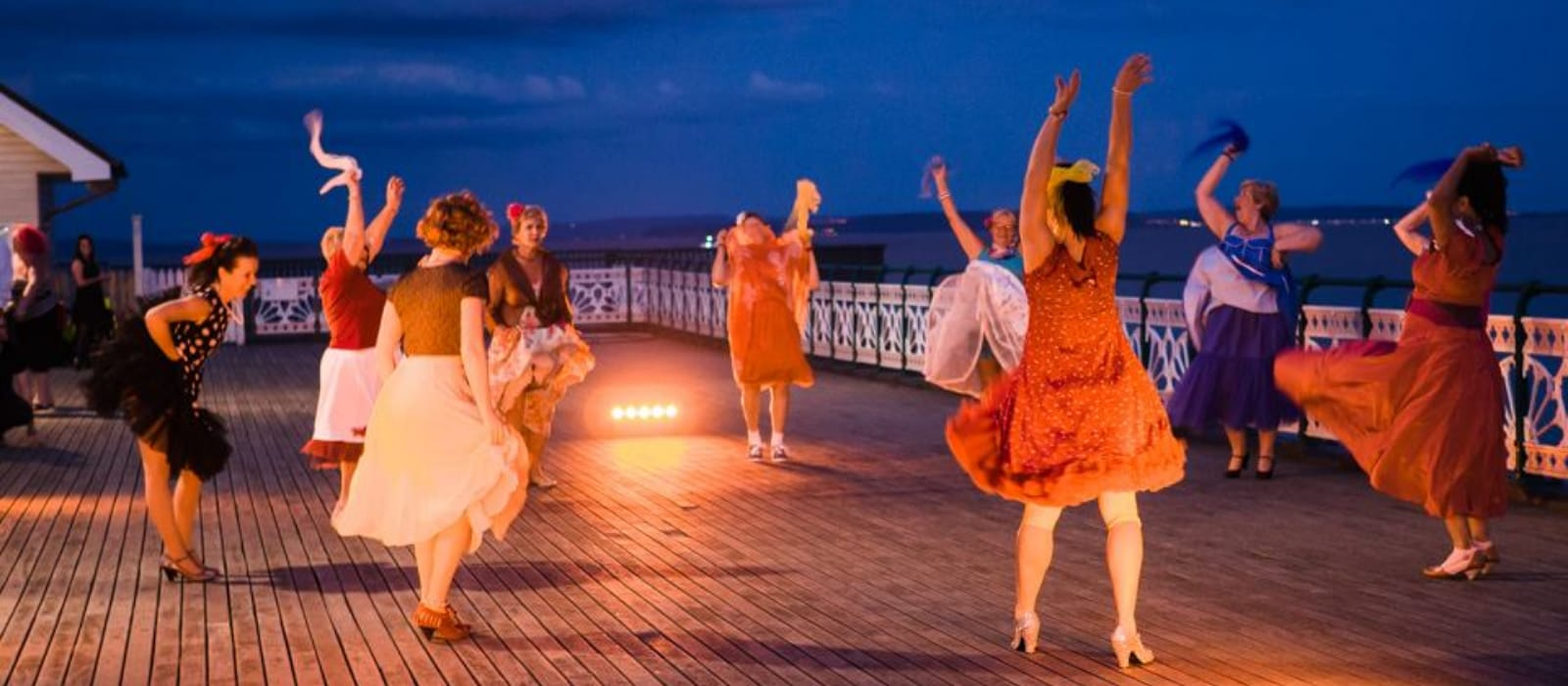 Penarth Pier Pavillion 50+ Dance Group performing in 1950s style dresses on the pier.