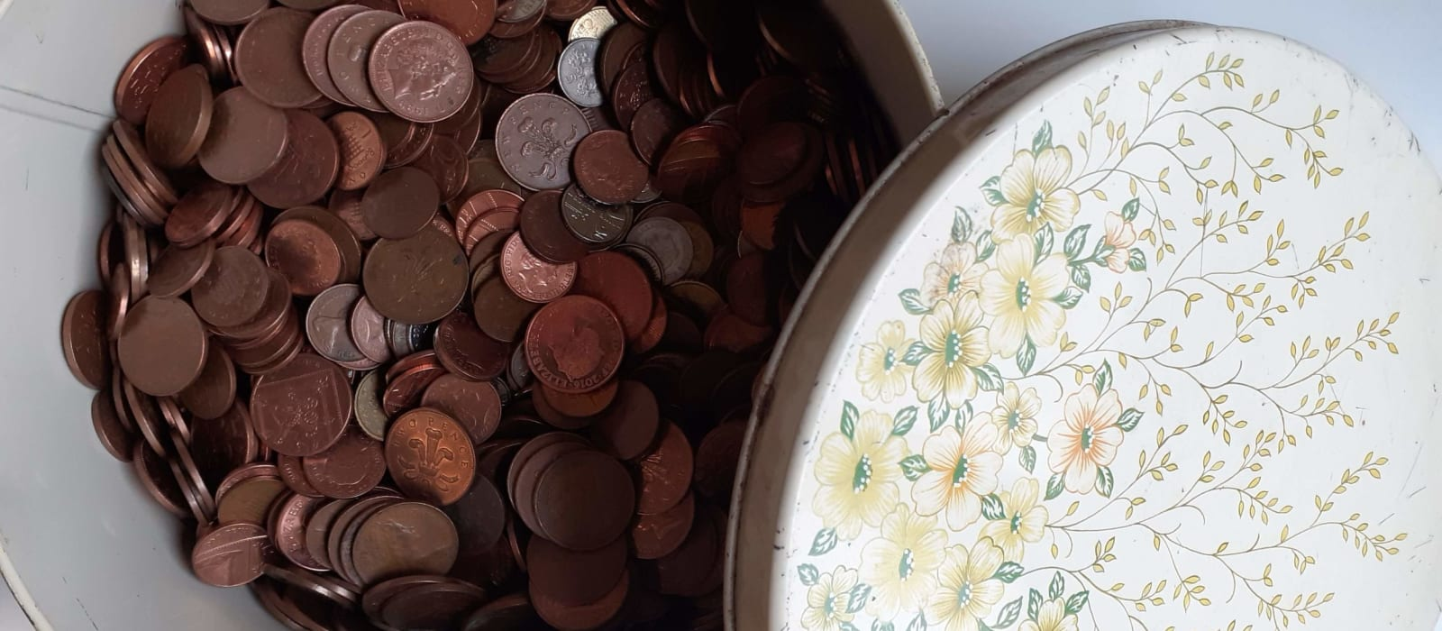 A round tin with floral decorations full of 1 and 2 pence coins.