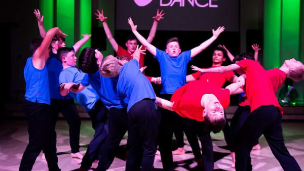 The boys dance group performing in red and blue t-shirts.