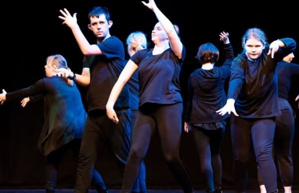Young dancers performing on stage in black outfits at the Schools Dance Festival.