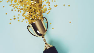 A gold trophy with gold star confetti against a light blue background.
