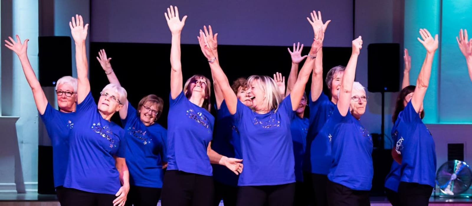NuWave dancers wearing matching blue t-shirts, grouped together and smiling with arms raised at the end of a performance.