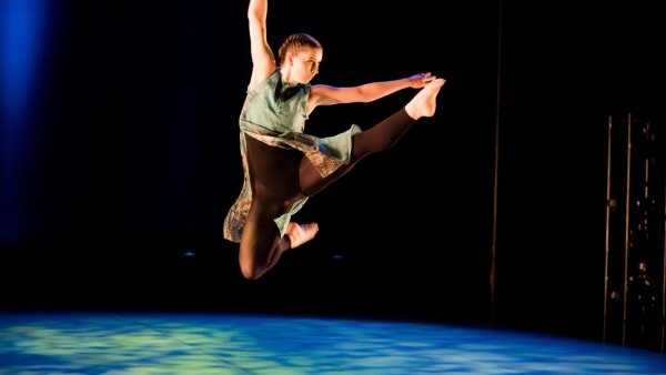 BTEC student jumping with leg raised on stage